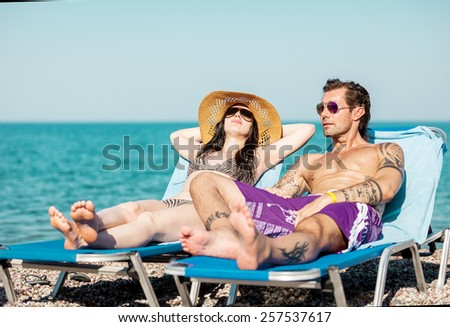 Photo of couple taking the sun at the beach while relaxing - stock photo