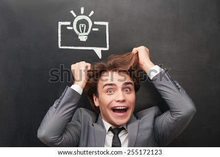 Photo of crazy young man on chalkboard background. Graphs painted with chalk on chalkboard - stock photo