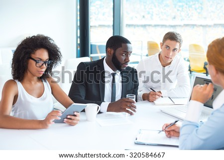Photo of creative multi ethnic business group. Mixed race business team using electronic devices and discussing project. White modern office interior with big window - stock photo
