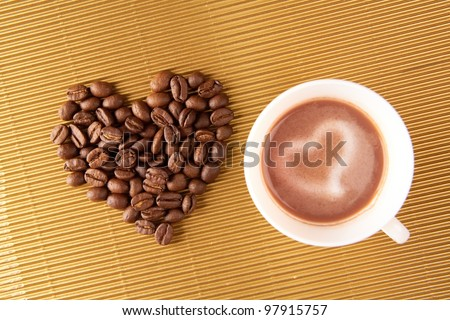 Photo of cup of coffee with shape of heart made up of beans near by - stock photo