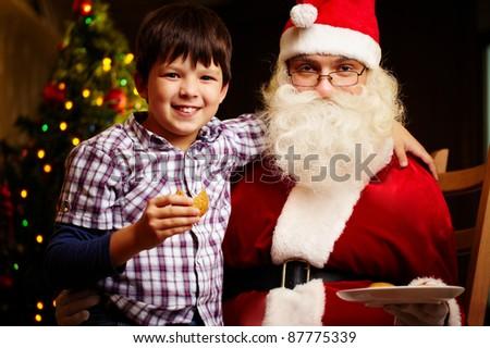 Photo of cute boy and Santa Claus looking at camera - stock photo