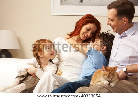Photo of cute boy embracing his pretty mother surrounded by playful daughter and their father - stock photo