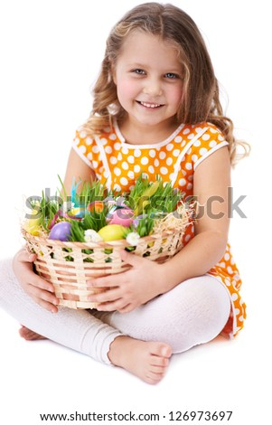 Photo of cute girl looking at camera while holding basket with colorful Easter eggs - stock photo
