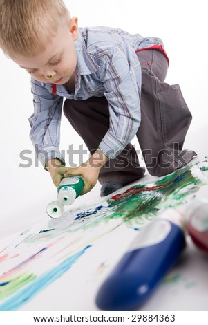Photo of cute lad painting something with colorful gouache - stock photo