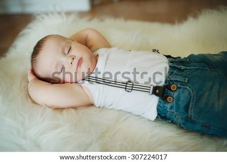 photo of cute little sleeping boy at fur - stock photo
