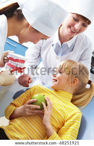 Photo of dentist teaching care dental hygiene little girl with assistant near by - stock photo