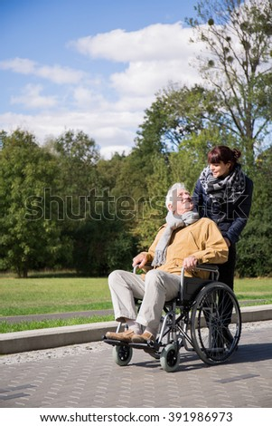 Photo of disabled man on wheelchair trip in park - stock photo