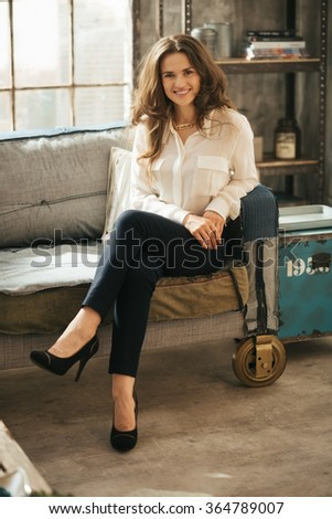 Photo of effortlessly stylish brunet woman with brown hairs sitting on the coach in loft apartment - stock photo