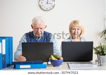 Photo of elderly business couple working at office - stock photo