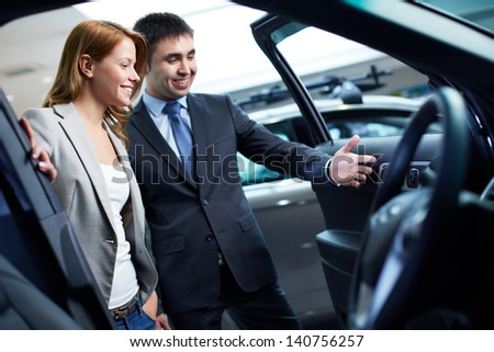 Photo of elegant woman listening to consultant in automobile center - stock photo