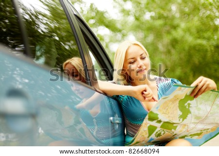 Photo of elegant woman sitting by her car and looking at map - stock photo