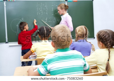 Photo of elementary student by blackboard looking at his teacher helping him - stock photo