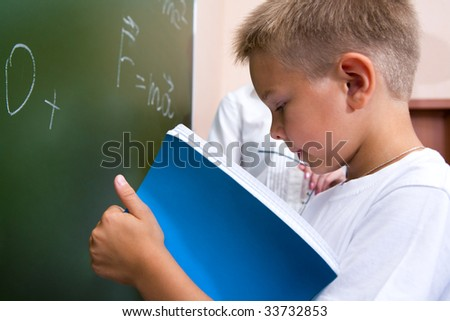 Photo of elementary student holding copybook and consulting his notes by the blackboard - stock photo