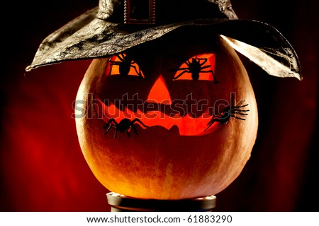 Photo of evil pumpkin with four spiders - stock photo