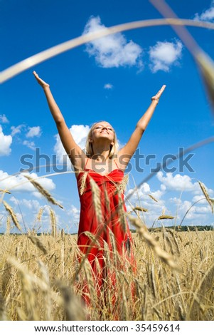 Photo of excited female in red dress standing with her arms raised in wheat field - stock photo