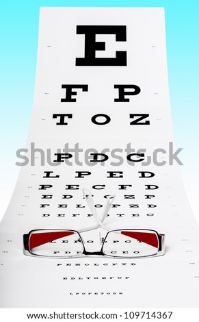 Photo of eye test chart and spectacles on a blue background - stock photo