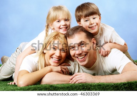 Photo of family members smiling at camera on blue background - stock photo