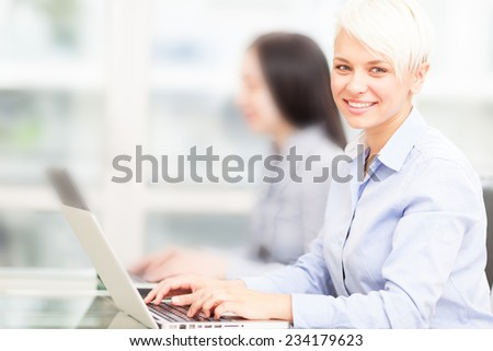 photo of female blonde employee working on her computer in office  - stock photo
