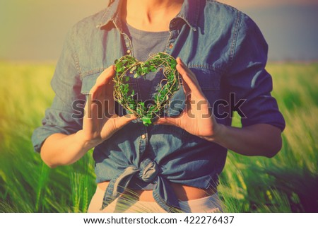 photo of female hands holding heart shaped toy in the field - stock photo