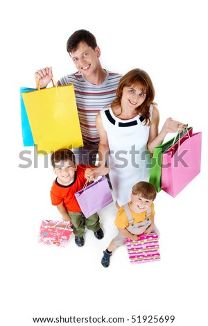 Photo of friendly parents and siblings with bags smiling at camera - stock photo
