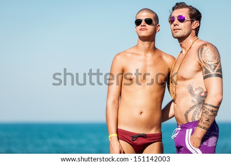 Photo of gay couple looking at the sun while hugging each other - stock photo