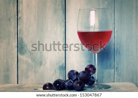 Photo of glass with pink wine and grapes - stock photo