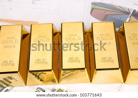 Photo of gold bars on graphs and statistics, studio shots, closeup - stock photo