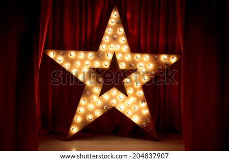 Photo of golden star with light bulbs on red velvet curtain on stage - stock photo