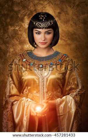Photo of gorgeous woman with Cleopatra makeup holding magic lighting ball - stock photo