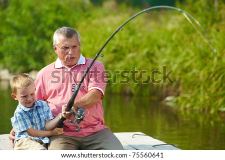 Photo of grandfather and grandson pulling rod together while fishing - stock photo
