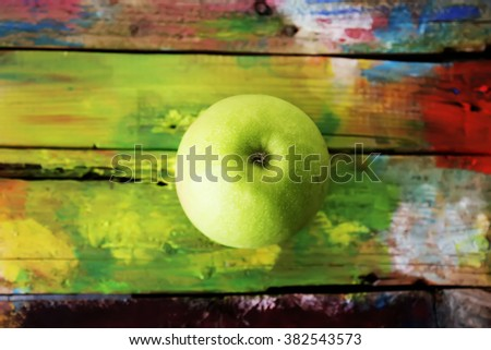 Photo of green apple on yellow wooden background - stock photo