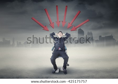 Photo of handicapped businessman sitting on the wheelchair and looks stressful, shot outdoors - stock photo