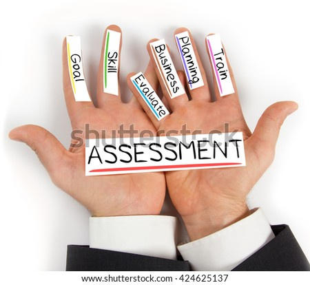 Photo of hands holding paper cards with ASSESSMENT concept words - stock photo