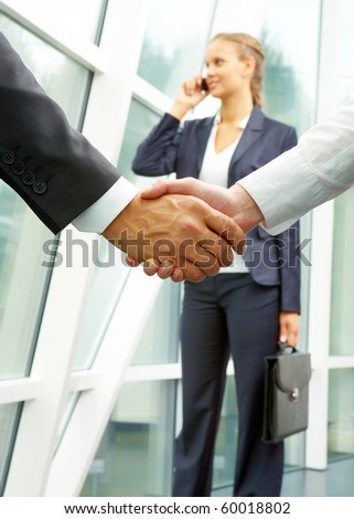 Photo of handshake of business partners after striking deal with calling female on background - stock photo