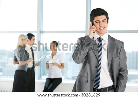 Photo of handsome employer calling his partner on background of working people - stock photo