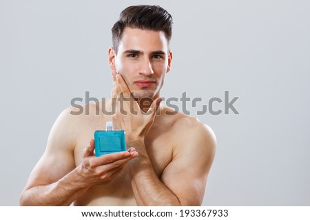 Photo of handsome man applying aftershave,Aftershave - stock photo