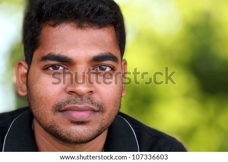 Photo of handsome middle-aged Indian/asian youth with content and satisfied look. The eyebrows are thick and prominent and hair is black and curly with unshaven stubble on the face. - stock photo