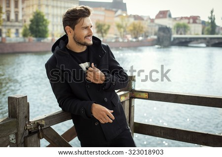 Photo of handsome smiling man in black coat in autumn scenery - stock photo