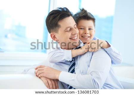 Photo of happy boy embracing his dad and looking at camera - stock photo