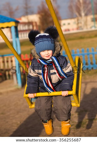 photo of Happy Boy Playing On A Swing - stock photo