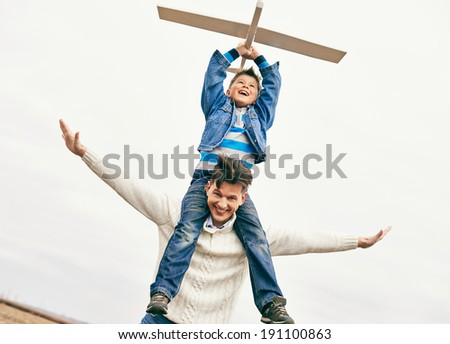 Photo of happy boy with toy airplane and his father against sky - stock photo