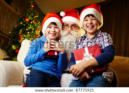 Photo of happy boys holding gifts with Santa Claus between them - stock photo