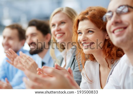 Photo of happy business people applauding at conference, focus on smiling female - stock photo