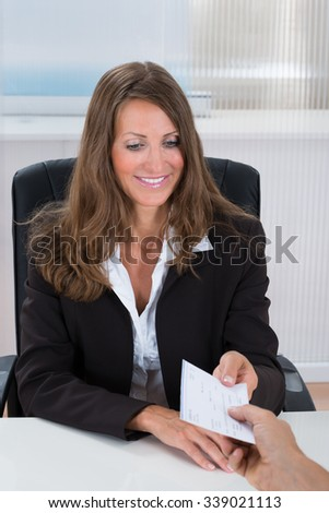 Photo Of Happy Businesswoman Receiving Cheque In Office - stock photo