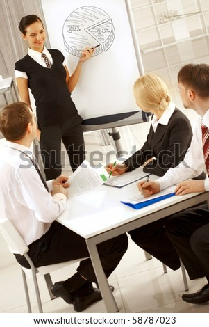 Photo of happy businesswoman sharing her ideas by whiteboard with partners - stock photo