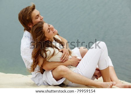 Photo of happy couple relaxing on sand during summer vacation - stock photo