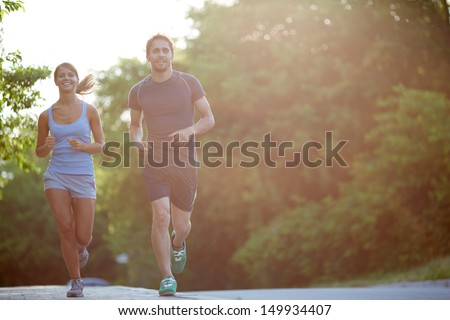 Photo of happy couple running outdoors - stock photo