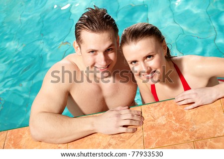Photo of happy couple smiling at camera in swimming pool - stock photo
