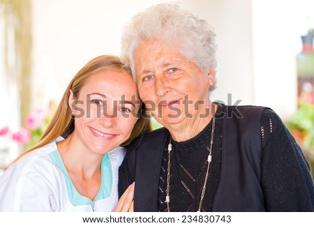 Photo of happy elderly woman with her caregiver - stock photo