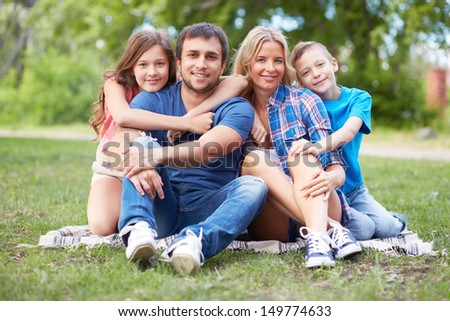 Photo of happy family of four sitting on grass during summer rest - stock photo